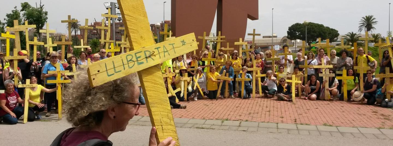 Imatge dels participants portant creus grogues de fusta a la rotonda Laia l'Arquera