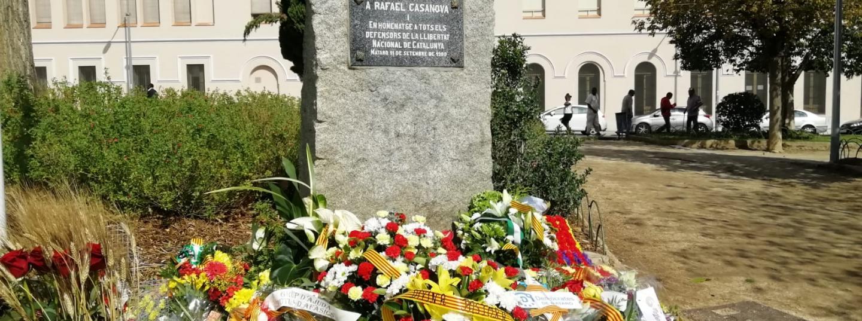 Les diverses ofrenes florals en el monòlit de la plaça Rafael Casanova de Mataró